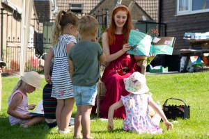 image of adult sharing story with children in park