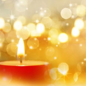 red candle with gold sparkle light background