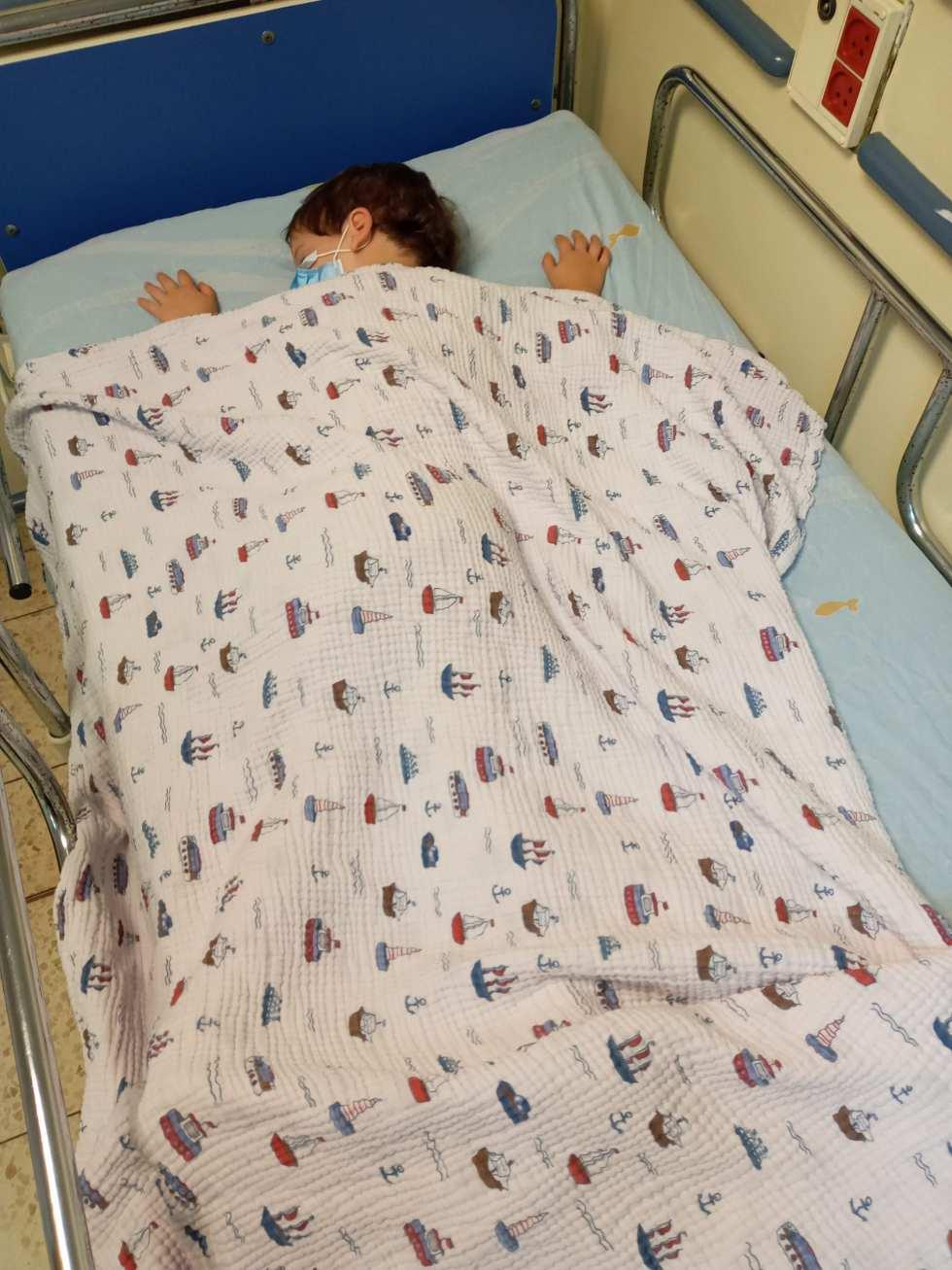 אחרי שקיבל את מנה ילד נרדם. לובש מסכה כי קורונה