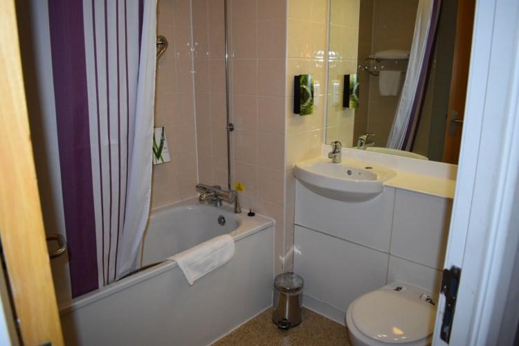 A hotel bathroom. Toilet, sink and bath.