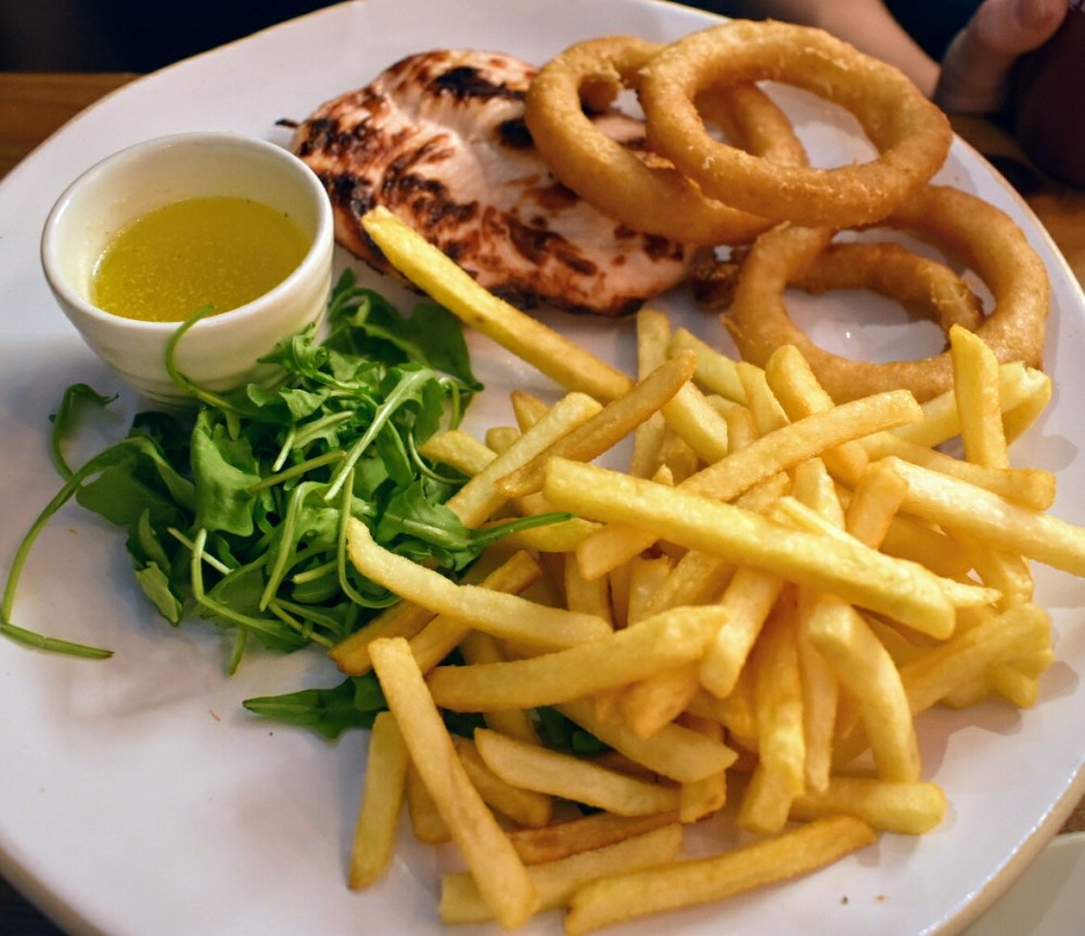 A plate of chips, chicken breast, rocket, onion rings and garlic butter.