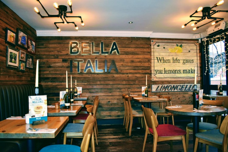 Tables in a restaurant with the sign saying Bella Italia on the wall behind.
