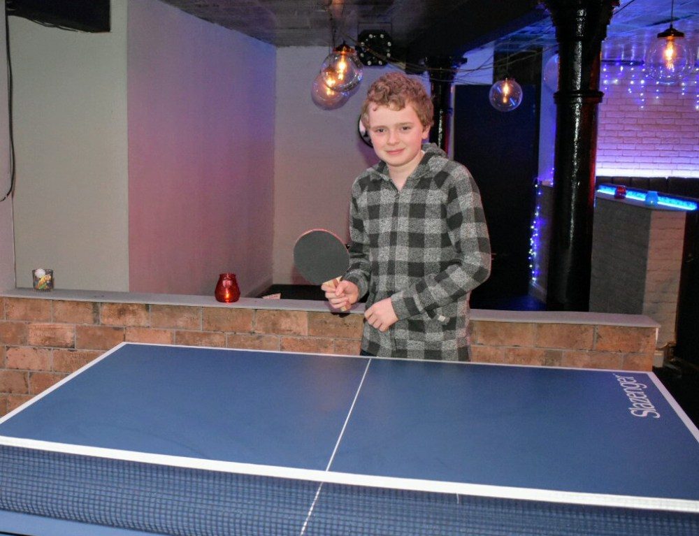 A boy at a table tennis table, holding a bat and smiling