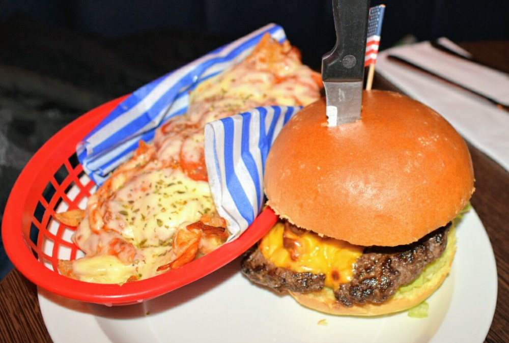 An apetising burger with a knife stuck in the top, next to a basket of peperoni and cheese topped fries