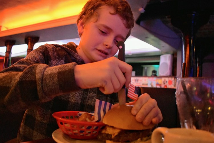 A boy taking the knife from the top of a burger