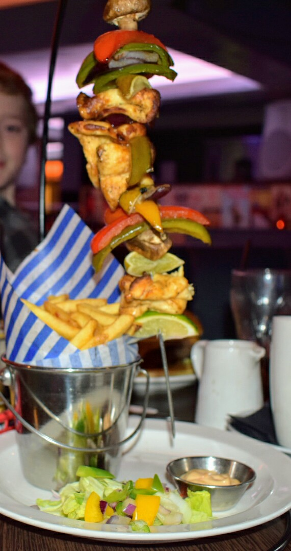 A hanging kebab dangling above a tin of fries