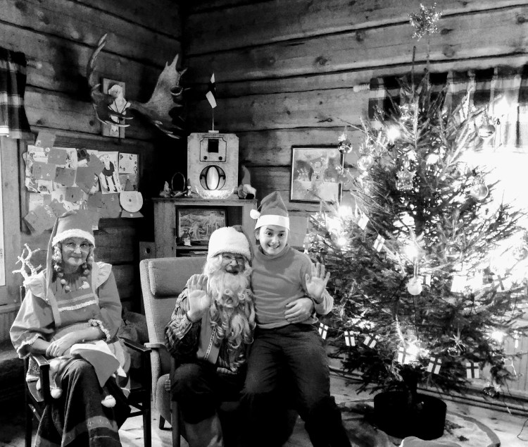A black and white photo of a child sat with Father Christmas and his wife. They are next to a Christmas tree.