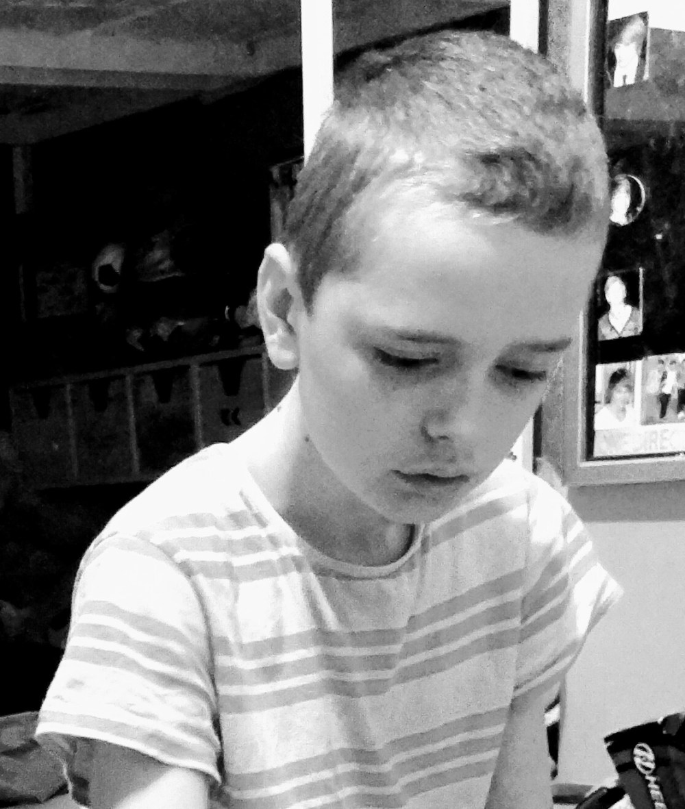 A black and white photo of a boy alone and looking sad