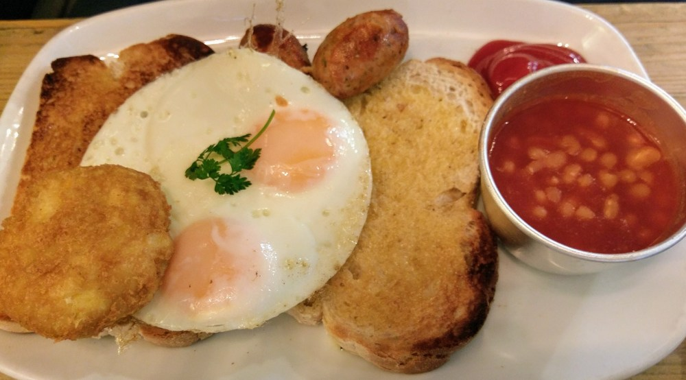 A cooked breakfast consisting of two slices of toast topped with a double egg, a small sausage