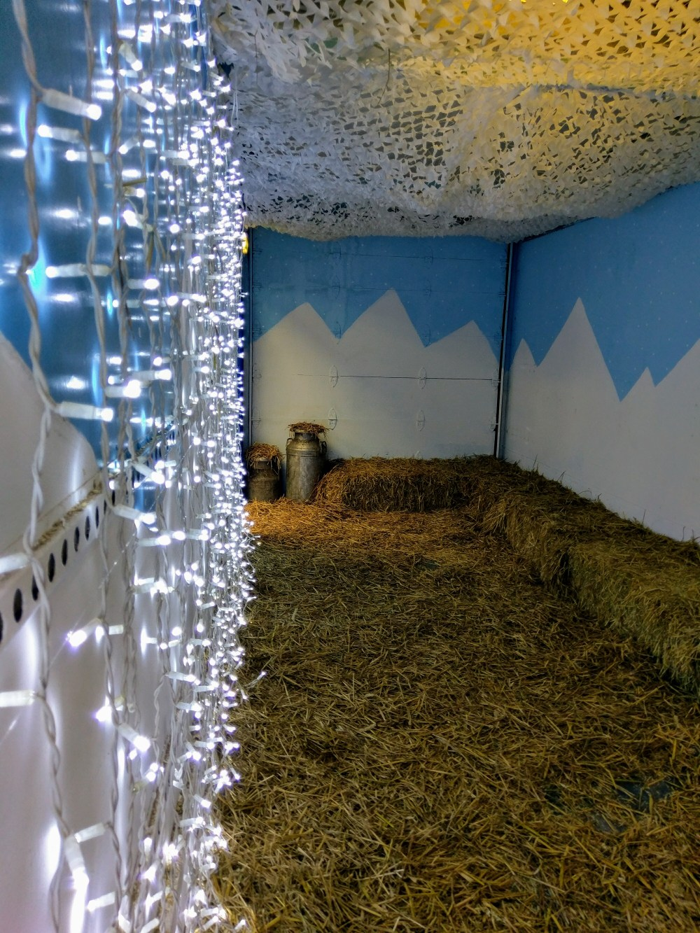 A room with hay on the floor and hay bales all around the edge. There are lights all down one wall.