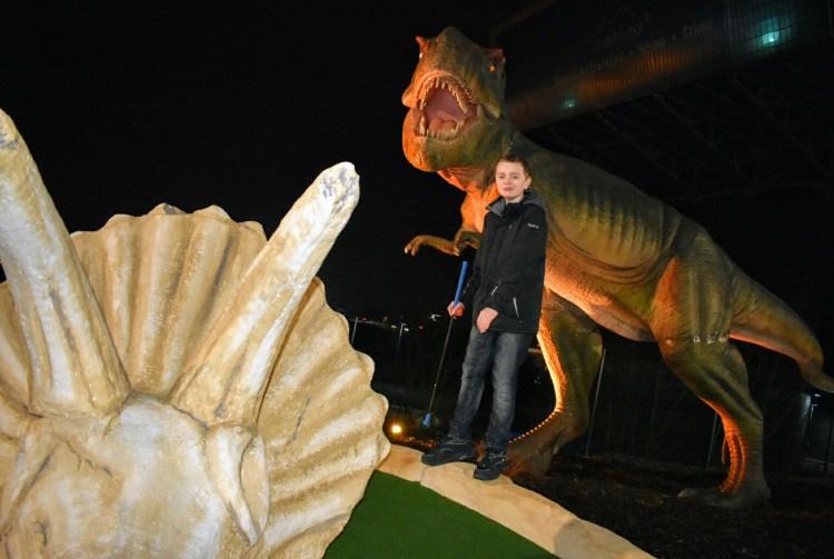 A boy with a golf club posing next to a dinosaur