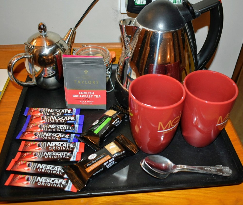 A tray with kettle, hot drinks, tea pot and biscuits