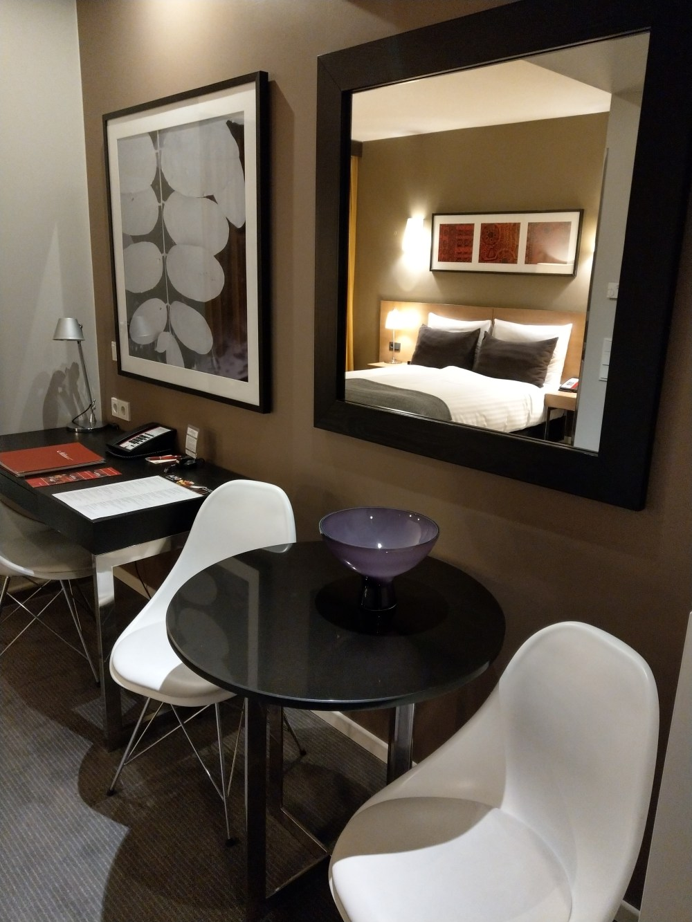 A hotel room at the adina apartment hotel berlin mitte. This picture is of the table and two chairs. In the mirror you can see a double bed