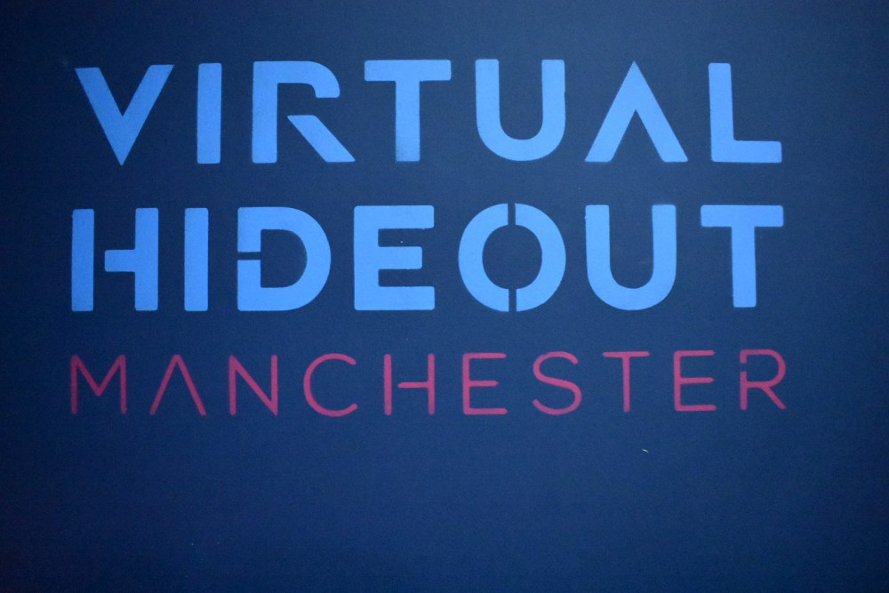 The words painted on the wall say Virtual hideout manchester