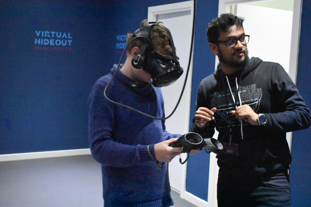 The host at Virtual hideout Manchester showing a boy how to play