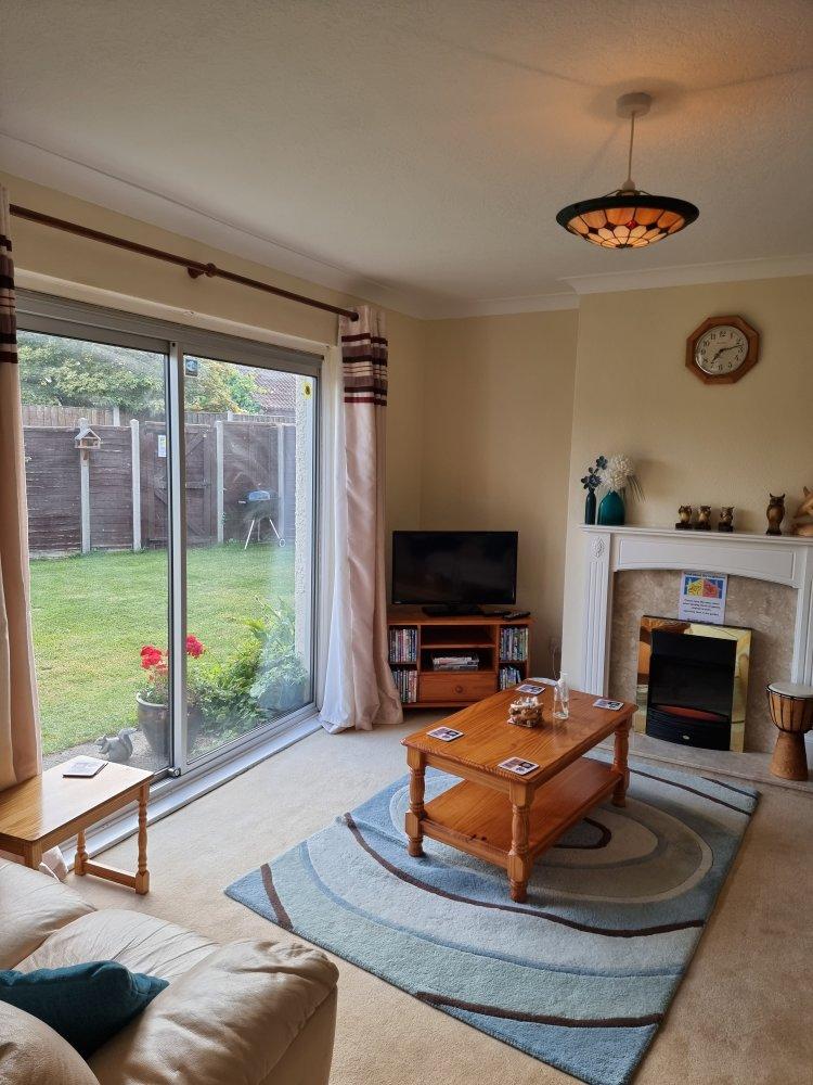 Living room at Endeavour short breaks. TV with dVDs. Patio doors to garden