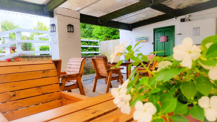 The covered outdoor dining area at the Hanging Gate pub in chapel-en-le-firth. Tables and chairs with flower decorations.