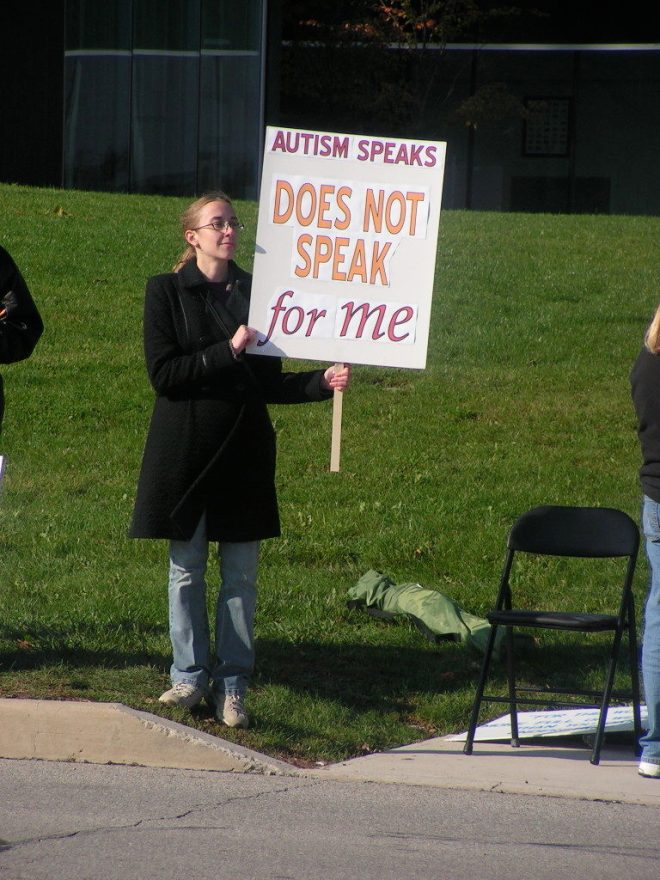 This is me holding a sign reading Autism Speaks does not speak for me