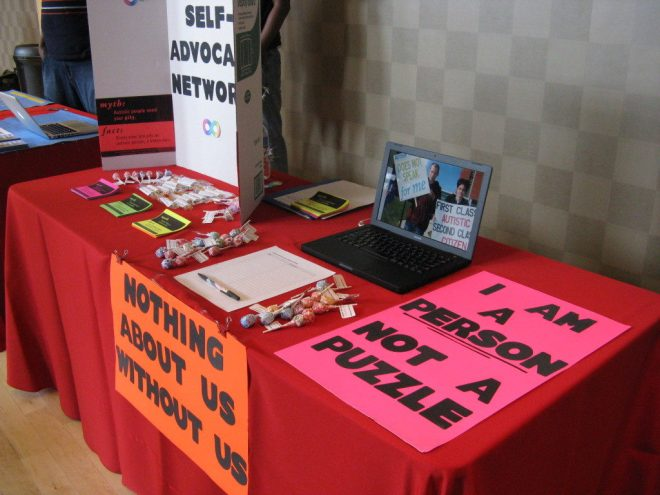 An ASAN booth. Featured are two signs, from left to right: NOTHING ABOUT US WITHOUT US and I AM A PERSON, NOT A PUZZLE.