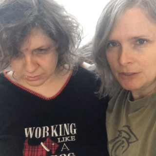 """Val and Jess are sitting together. Jess is wearing pj's that are black with red trim. The front of Jess shirt says """"Working Like A Dog"""" Val has her arm around Jess. Val is wearing an olive green t-shirt."""