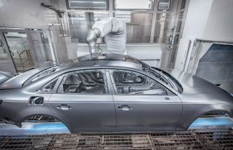 Protecting the environment and cutting costs: With overspray-free painting, Audi is now able to apply two different colors in the same painting process. A robot-controlled high-precision instrument measures the laser-brazed seam between the car's roof and side panel frame. An applicator then applies a black paint specially developed for this method onto the body in strips, with millimeter precision but without spray mist.