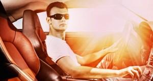 Muž řídící auto ve slunci
