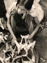 photographie de Marc Riboud : Une fillette de dix ans vend des répliques miniatures d'avions MIG Hanoi, Nord Vietnam 1969