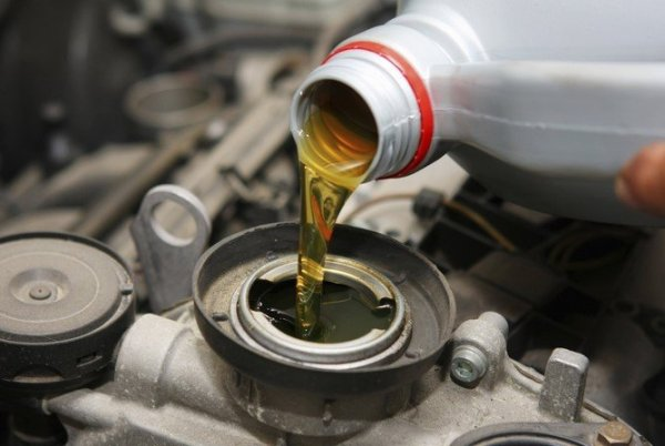 engine oil being poured into a car engine