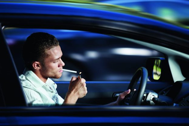 A young man lit a cigarette in a car at speed