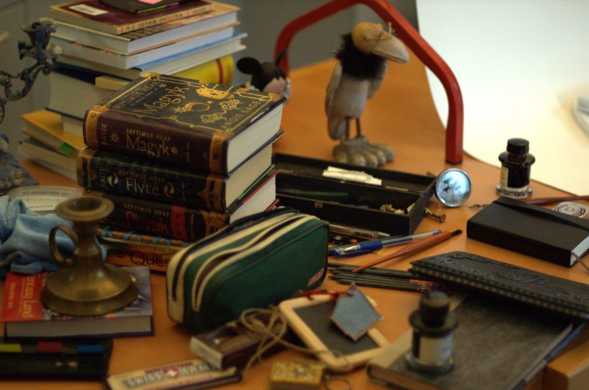 Chaos - Auf einem Tisch liegen Stapel Bücher, ein Kerzenständer, eine Raben-Figur, Stifte, ein Mäppchen eine alte Schiefertafel und Schieferstifte verstreut.