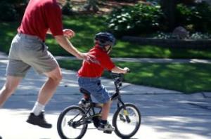 Padre ayudando a su hijo a montar en bicileta