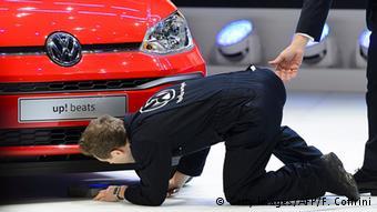 Британский комик Саймон Бродкин в костюме механика высмеивает Volkswagen на презентации в Женеве