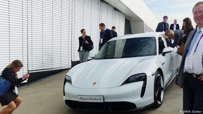 Люди рассматривают электромобиль Porsche Taycan