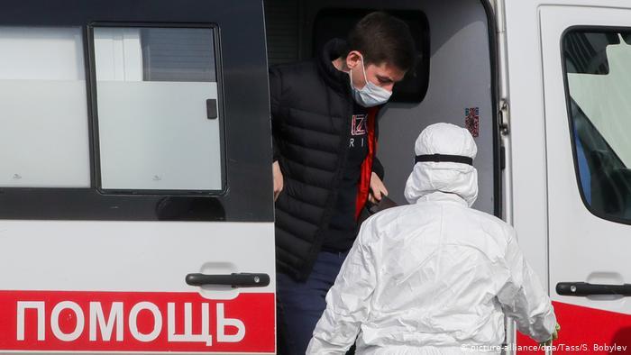 Машина скорой помощи с медиком в защитном костюме и пациентом в маске