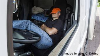 Водитель отдыхает в кабине грузовика
