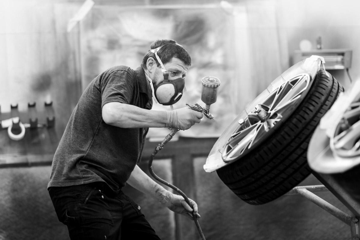 black and white of a spray painter refurbishing an alloy wheel.