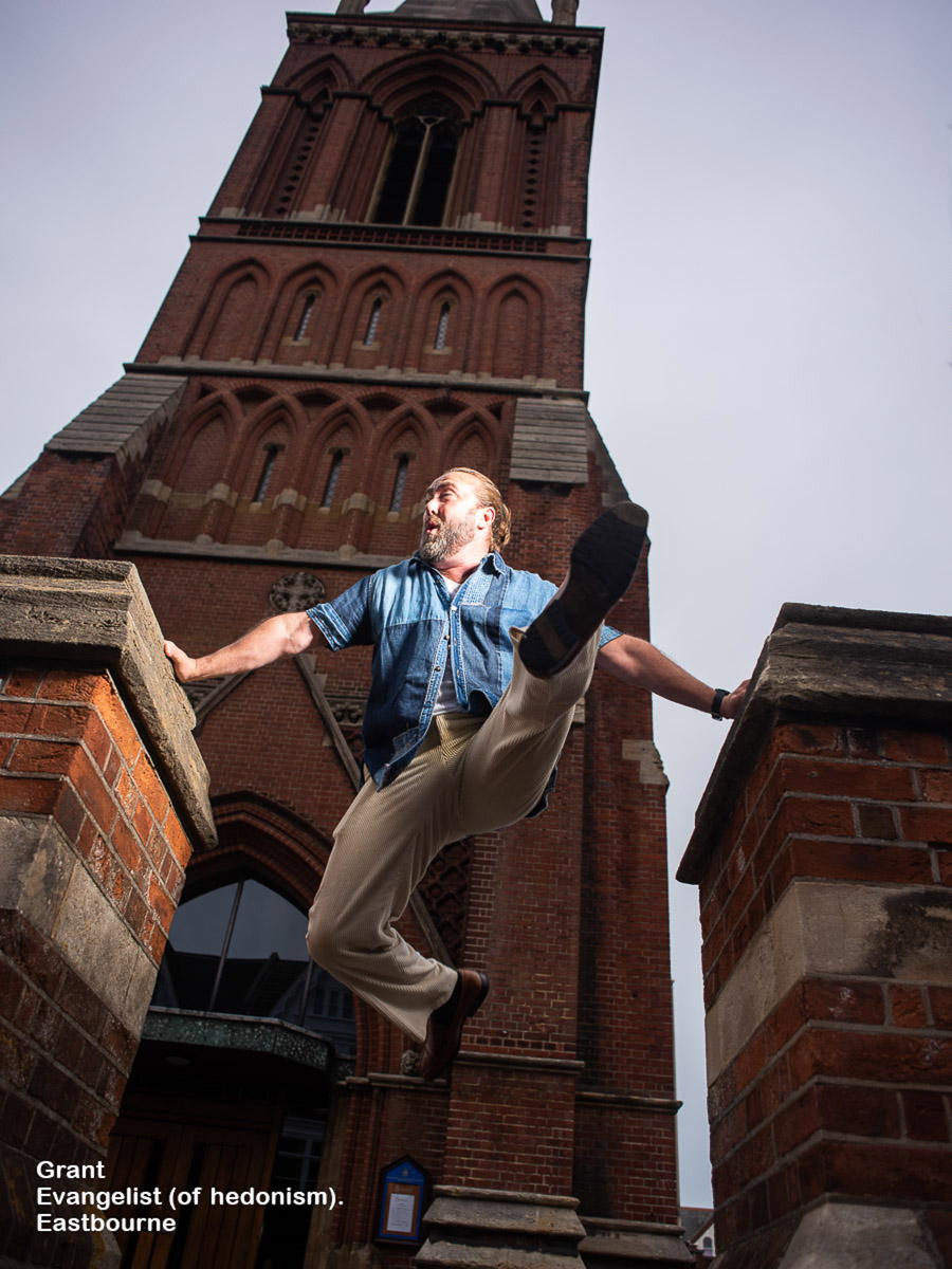 A man with a manbun leaps outside a church in Eastbourne