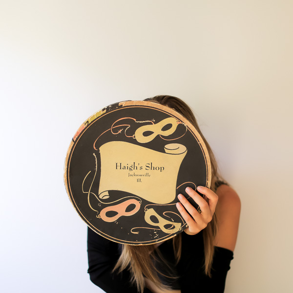 woman covering her face with a vintage hat box