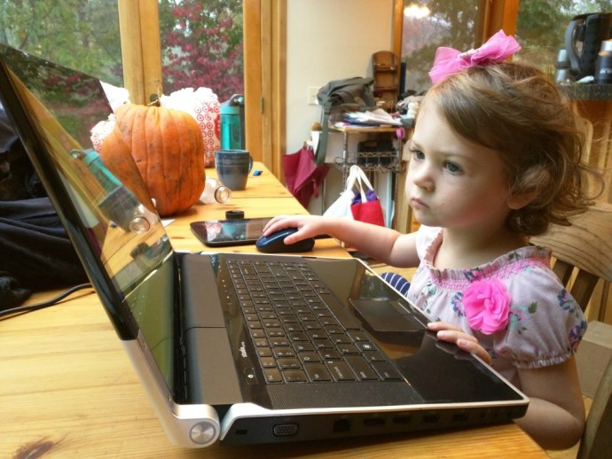 Ylva, age 3, trying to use a large laptop