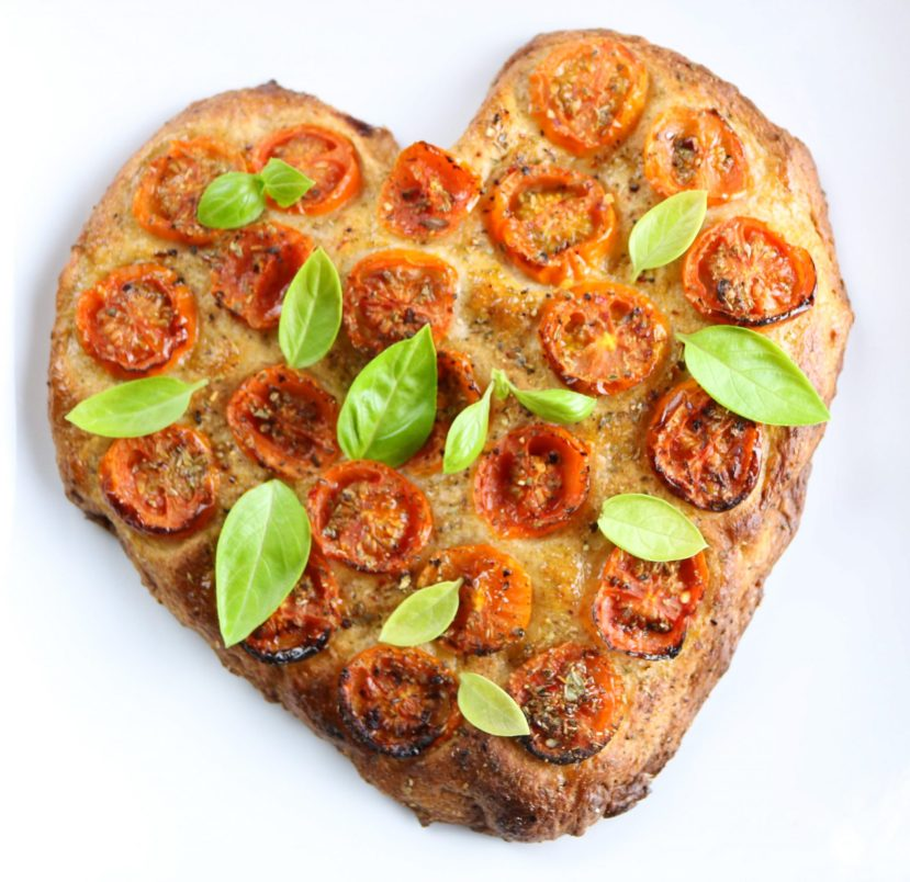 Heart shaped focaccia with cherry tomatoes and fresh basil.