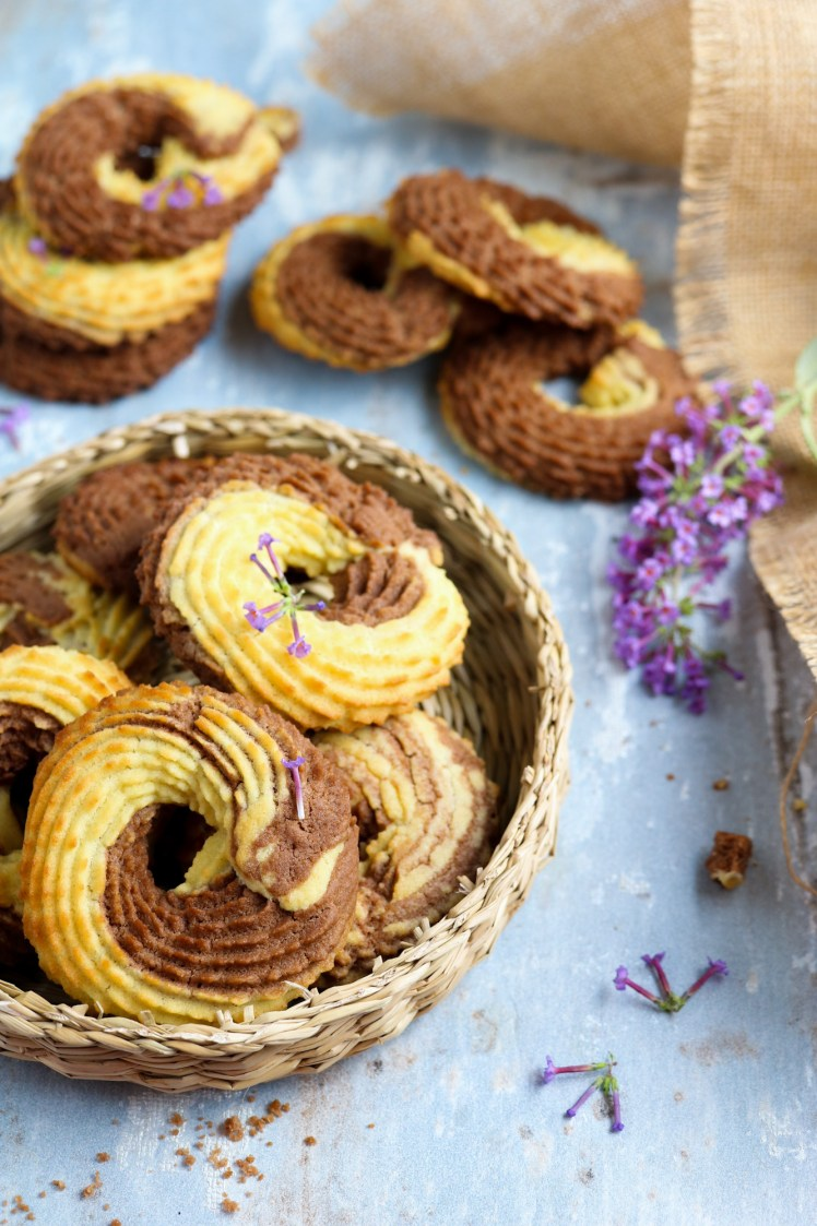 Vegan Whipped Cookies rings with cocoa powder nicely arranged on a wicker plate decorated with puple flowers bottom left
