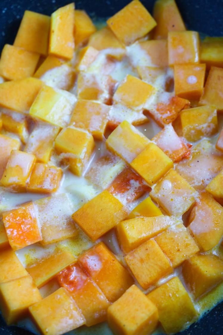 cubed butternut squash in a pan with plantbased milk for