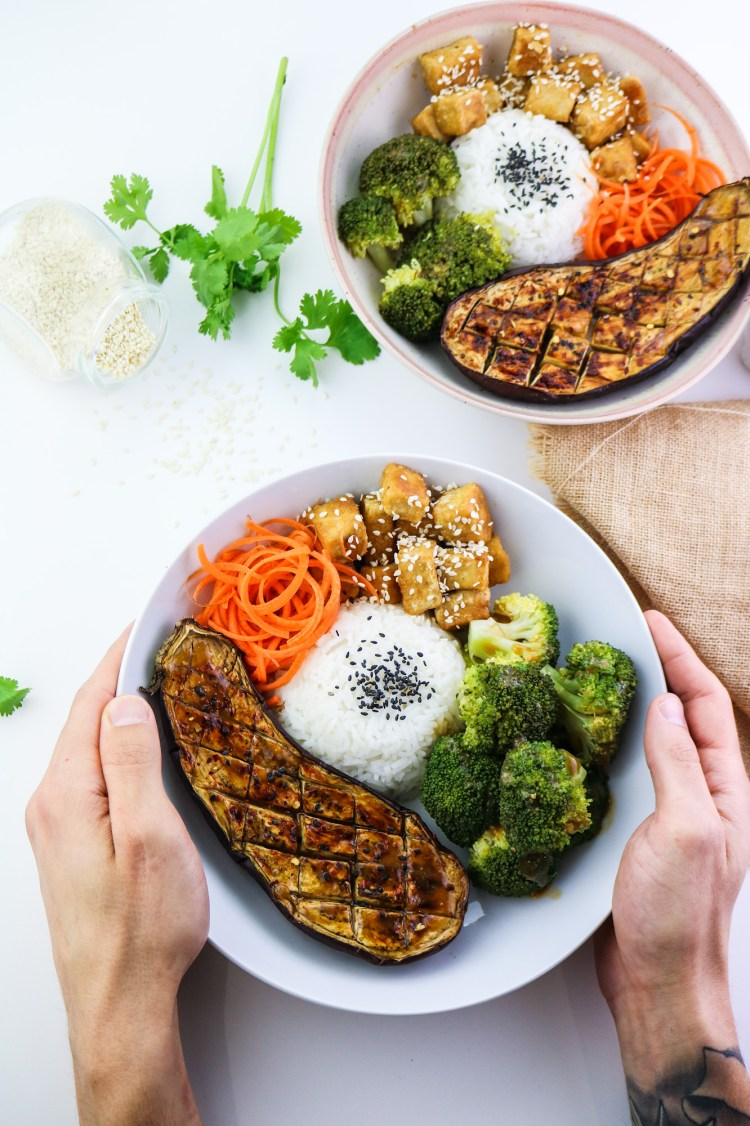 Tofu, Aubergine & Broccoli Miso Bowl with hands holding bowl