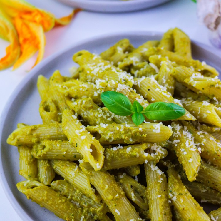 Courgette blossom pesto pasta on a flat dish showcasing the bright colours of the recipe