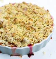 Amaretto & Rhubarb crumble on a grey, round ceramic dish on a white surface with almond shavings close up for feature image