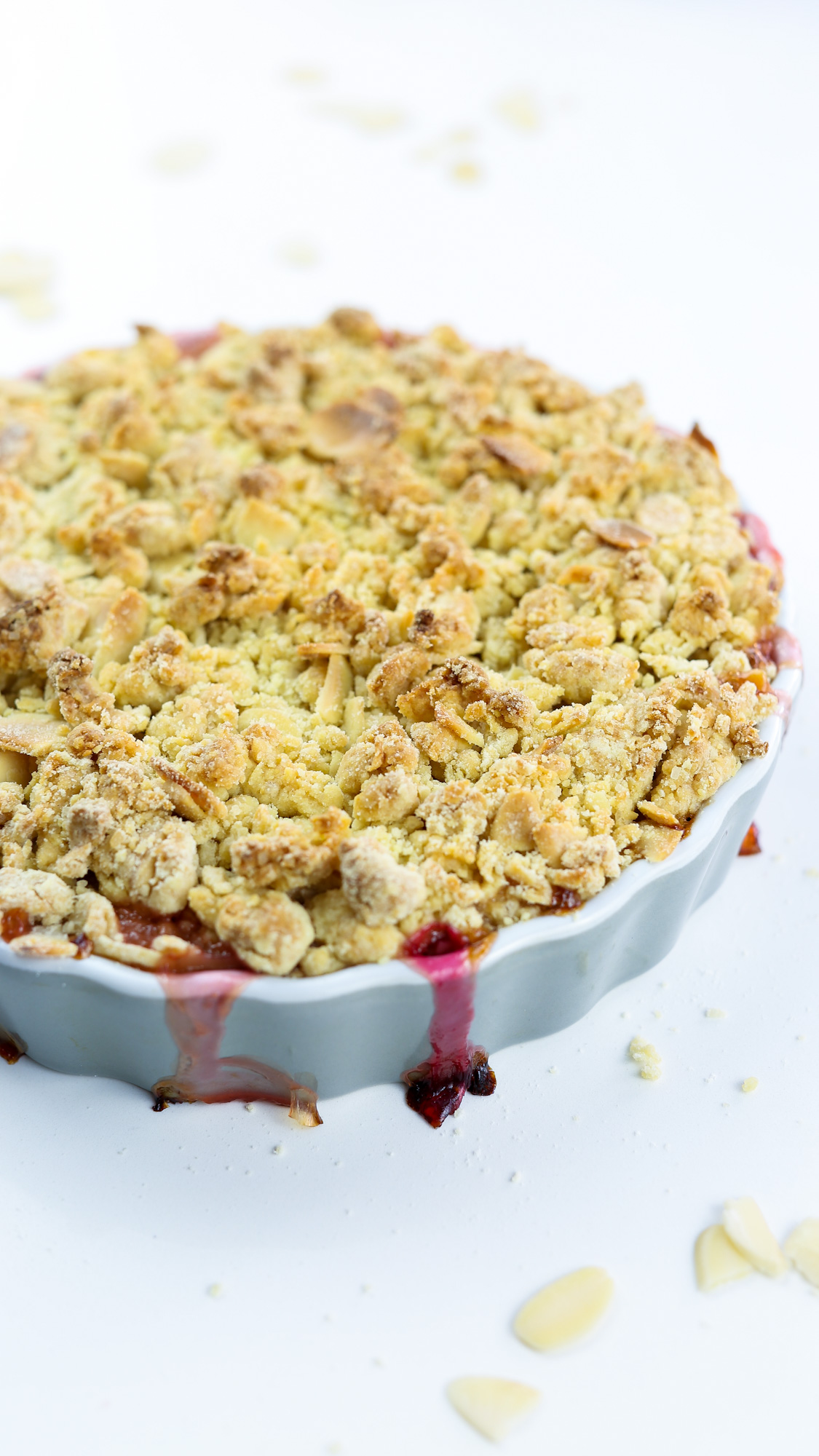 vegan Amaretto & Rhubarb crumble on a grey, round ceramic dish on a white surface with almond shavings