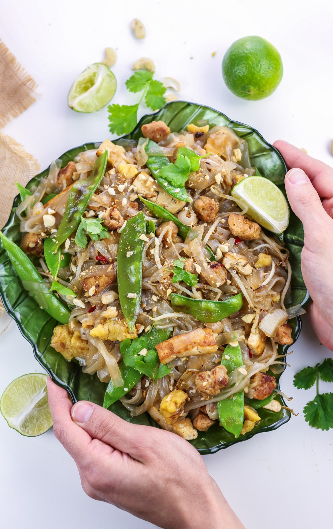 noodles and vegetables pad thai style served on a leaf shaped green plate, topped with cashews, lime wedges and cilantro leaves plate hold by both hands