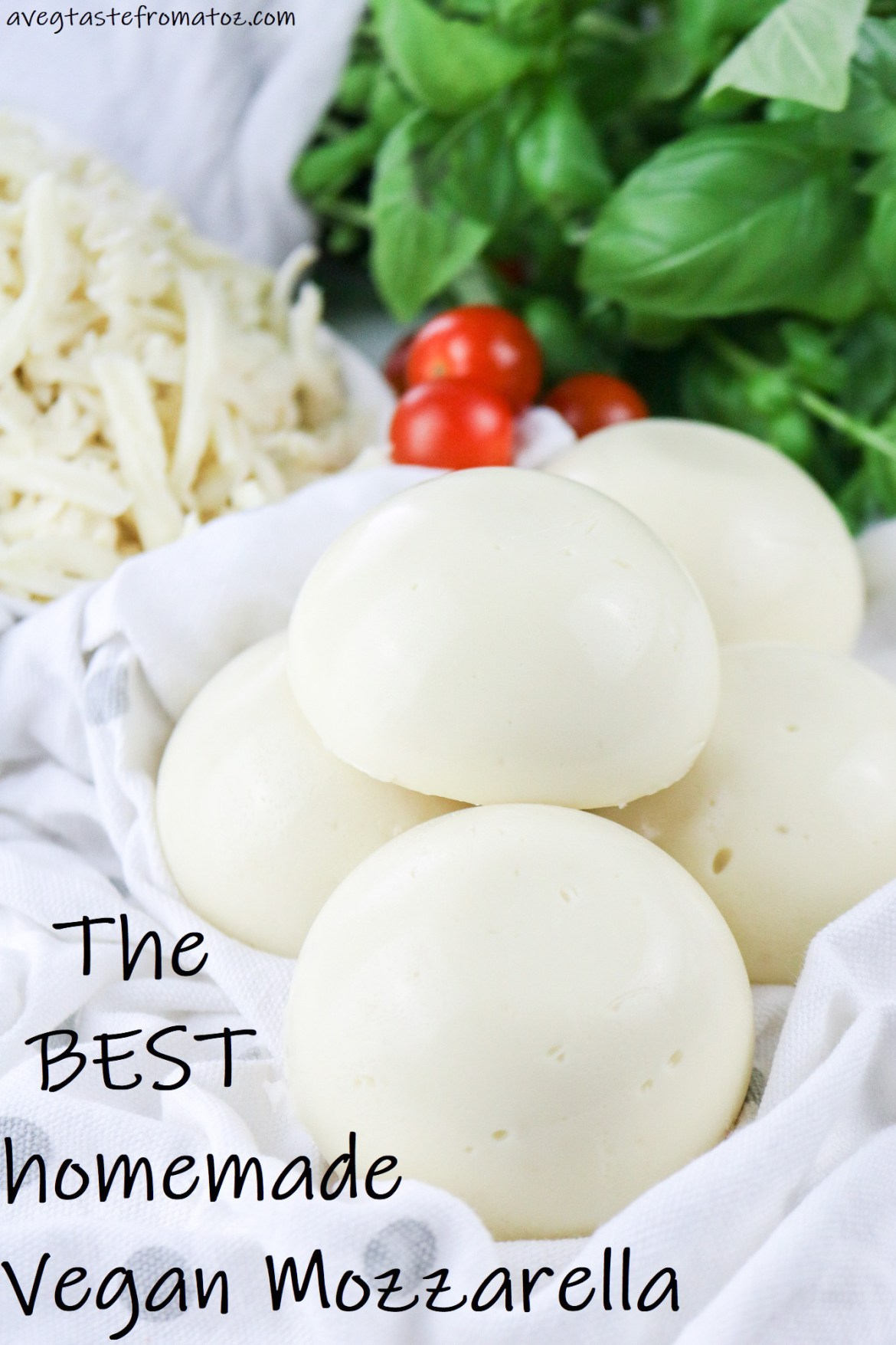 Vegan Mozzarella semi spheres on a white cloth with grey polka dots on a background of grated mozzarella shavings, cherry tomatoes and fresh basil with black text saying the best vegan mozzarella, image to be shared on social networks like pinterest