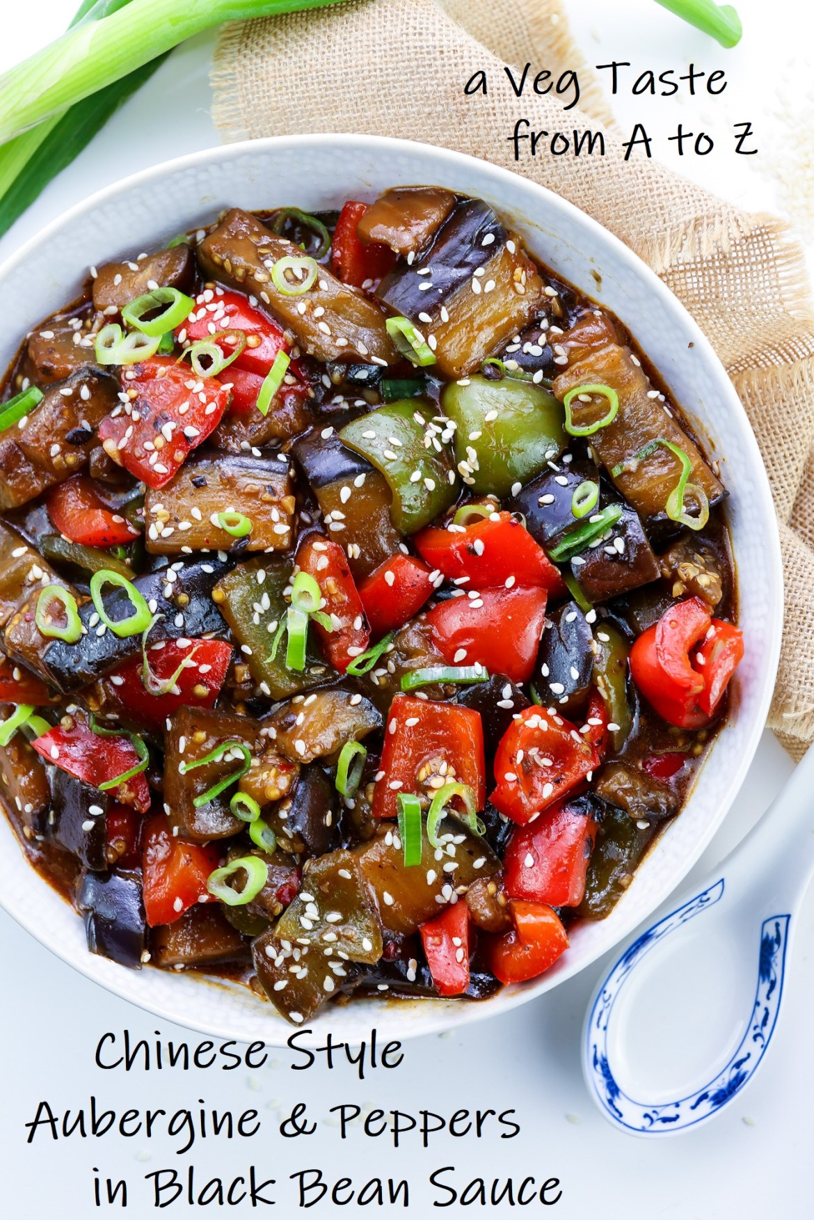 Vegan Aubergine & Peppers in Black Bean Sauce in a white bowl topped with green onions and sesame seeds and black text over image with the name of the recipe