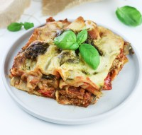 slice of creamy veggie lasagna with pesto and mozzarella sauce topped with basil leaves